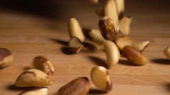 Brazil nuts fall onto table in slow motion Stock Footage