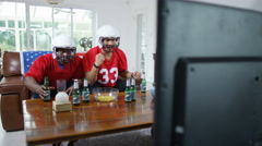 4K 2 friends hanging out together & watching American football game on TV - stock footage