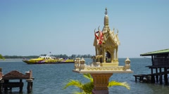 THAILAND, CIRCA 2015: Buddhist altar on marina and passing by ship on background Stock Footage