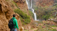 Nature photographer with tripod going to shoot waterfall with his dog Stock Footage