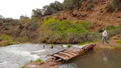 Girl cross bridge near Ouzoud Waterfalls, Morocco, Africa Stock Footage