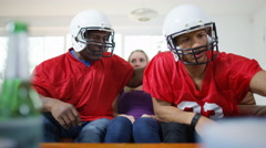4K Young woman sitting between 2 rowdy friends watching American football game  Stock Footage