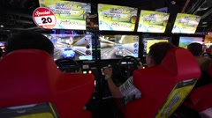 Kids playing arcade video game at an amusement park in MBK mall Stock Footage
