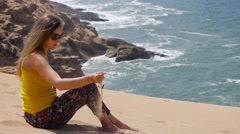 Young woman sitting on sand and play with sand with sea ocean rocks on Stock Footage