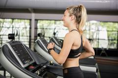 Woman walking on treadmill - stock photo