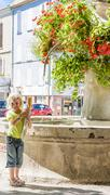 little girl with baguette at fountain, Oraison, Provence, France - stock photo