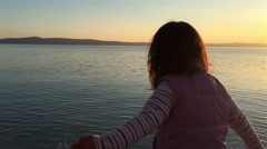 Slow motion view of small girl throwing stones into sea Stock Footage