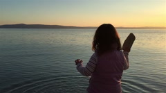 Little girl throwing  pebbles into sea at sunset - stock footage