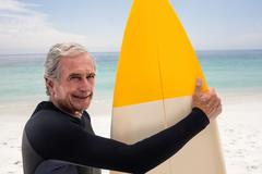 Portrait of senior man in wetsuit holding a surfboard - stock photo