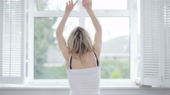 4K Woman waking up & stretching in front of window in the morning Stock Footage