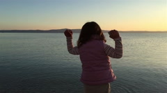 Small girl throwing pebbles into sea - stock footage