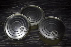 Three conserve can on wooden background - stock photo