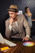 Creative businessman using computer and graphic tablet - stock photo