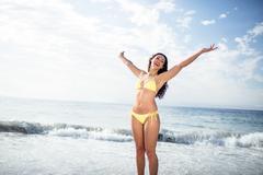 Carefree woman in bikini standing on the beach - stock photo