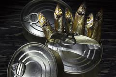 Close-up of Tinned capelin fish on wooden background - stock photo