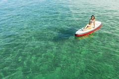Woman relaxing over a paddle surfboard Stock Photos