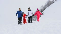 Family of 4 running down in snowy slope Stock Footage