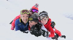 Portrait of family having fun laid in the snow Stock Footage
