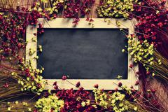 blank chalkboard surrounded by flowers - stock photo