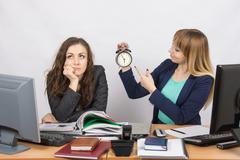 Two young pretty business woman sitting at a office table is divided into two Kuvituskuvat