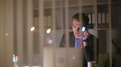 The young businessman works till late evening - stock footage