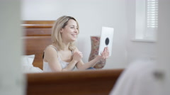 4K Attractive woman relaxing in bedroom, making video call with tablet computer. Stock Footage
