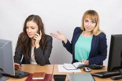 The girl in the office puzzled indicates colleague talking on the phone - stock photo