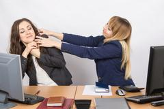 The girl in the office workplace trying to stifle a colleague - stock photo