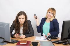 Two young pretty business woman sitting at a office table is divided into two Stock Photos