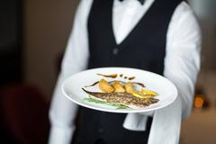 Handsome waiter presenting meal - stock photo