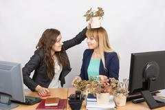 Frustrated office employee puts on a head-grower colleagues with a flower pot Stock Photos
