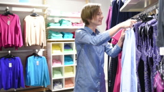 sale, clothes , shopping, people concept - happy young woman choosing between - stock footage