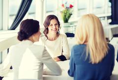 Happy women meeting and talking at restaurant Kuvituskuvat