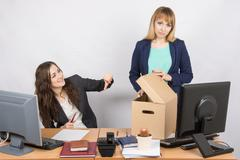 Office woman with a humiliating gesture unsettled the dismissed colleague Stock Photos