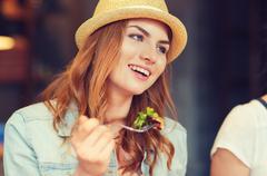 happy young woman eating salad at bar or pub - stock photo