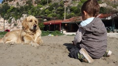 Mean child throws sand into dog - stock footage