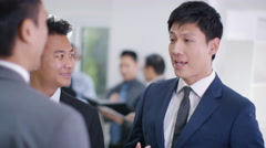4K Smiling Asian business group shake hands & discuss business - stock footage