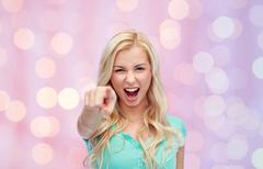 happy young woman pointing finger to you - stock photo