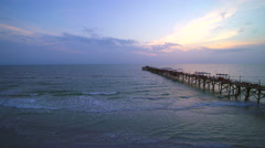 Pull away from pier at beach during sunset Stock Footage