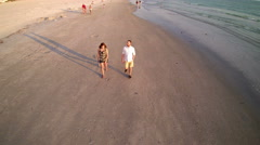 Couple walking along shore line at beach - stock footage