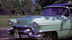 1959: Teal Cadillac 4 door classic car parked in outdoor green space. Stock Footage