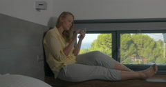 Woman sitting on window-sill and using phone - stock footage