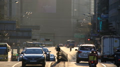 City traffic on uphill road in downtown Seoul at sunset Stock Footage