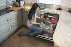 Woman arranging plates in dish washer - stock photo