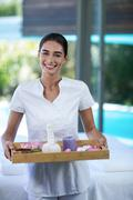 Female masseur holding a tray with spa therapy products - stock photo