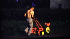 1959: Shirtless man mowing thick weeds lawn with industrial machine. Stock Footage