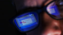 Uploading spyware reflected in man's glasses Stock Footage