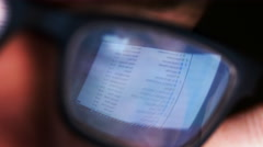 Email list reflected in man's glasses - stock footage