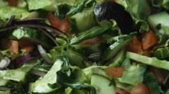 Housewife hands flavouring delicious vegetable salad with Italian olive oilin a Stock Footage