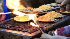 Man making famous grilled scallops at Myeongdong street in Seoul Stock Footage